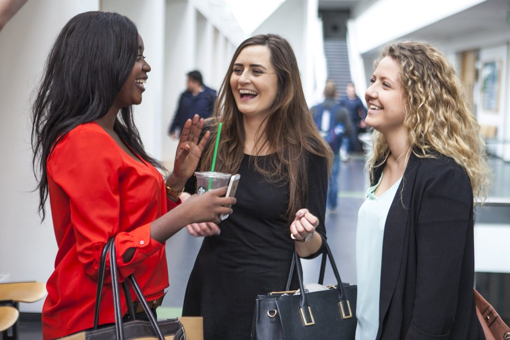 Three women discussing something and smiling